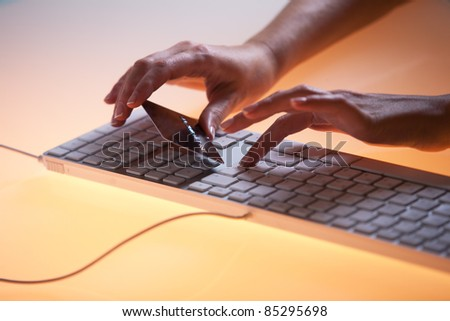Woman's right hand holding a credit card above a keyboard getting ready to enter data - stock photo