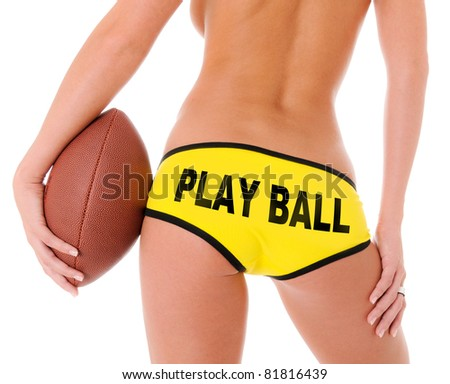 Woman's Sexy Backside Holding a Football and Yellow shorts that reads Play Ball - stock photo