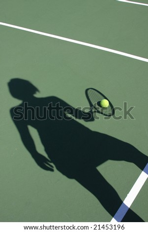 Woman's shadow holding racket with tennis ball on court - stock photo
