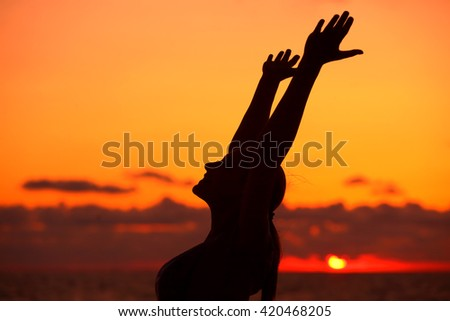 Woman's silhouette on sunset background, doing yoga exercise outdoors on the beach in the evening, enjoying life, happy summer holidays - stock photo