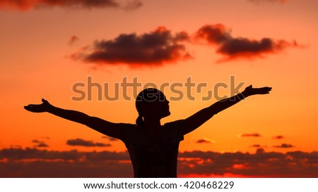 Woman's silhouette on sunset light, happy girl with raised up hands standing on the beach and enjoying warm summer evening, doing yoga exercise outdoors - stock photo