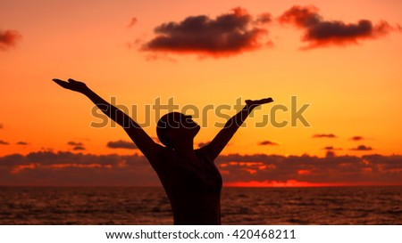 Woman's silhouette over sunset background, happy girl with raised up hands standing on the beach and looking up in the sky, enjoying summer vacation - stock photo