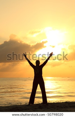 woman's silhouette with her hands raised in the sunset - stock photo
