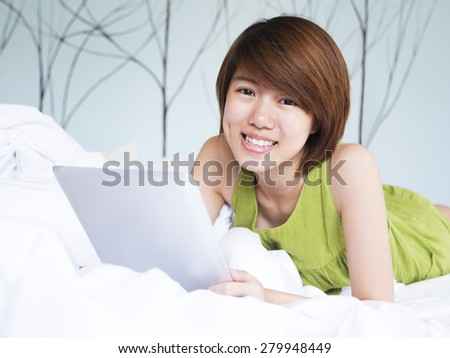 Woman's smiling while she's playing tablet - stock photo