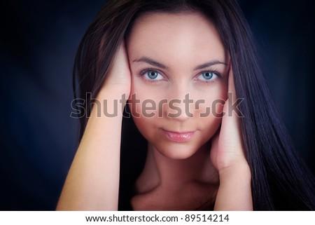 Woman's studio portrait. Face against dark background. - stock photo