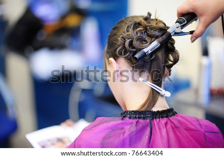 Woman's stylist's hands making a fancy hairstyle - stock photo