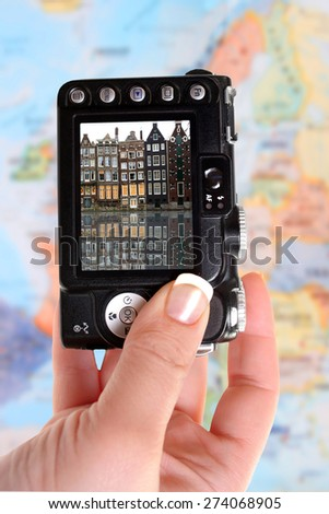 Woman's tourist hand holds camera taking a picture of Amsterdam Holland with blurred map of Europe in the background - stock photo