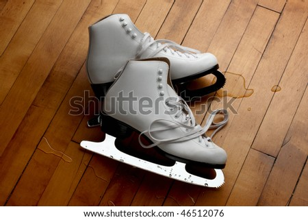 Woman's white figure skates shot on wooden floor with small pools of melted ice - stock photo