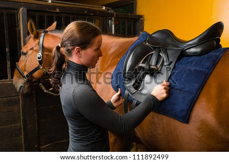 Woman saddle a horse in the stall