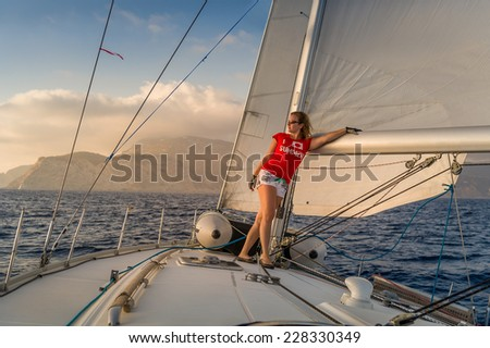 Woman sailor stays at deck of sailing yacht going at full sails to sunset