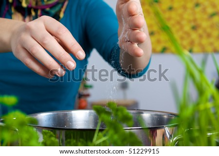 Woman salting a meal in a pot behind of herbs, parsley and chives - stock photo