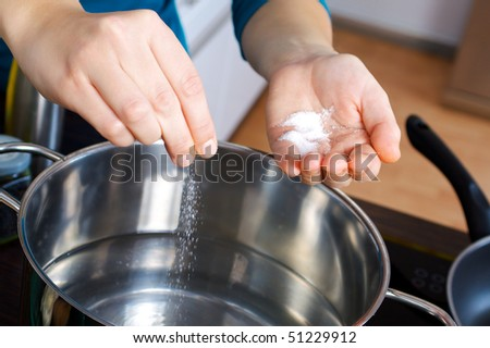 Woman salting water in a pot on a stove in the kitchen - stock photo