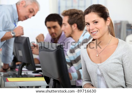 Woman sat by computer in class
