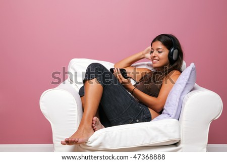 Woman sat in an armchair wearing headphones listening to a music video on her mp3 player - stock photo