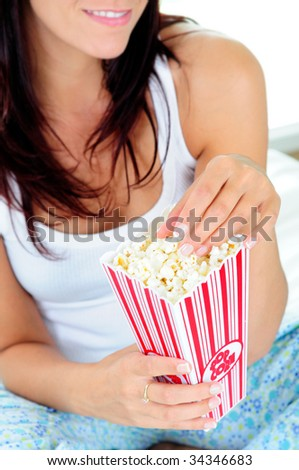 Woman Sat On Her Bed Eating Popcorn - stock photo