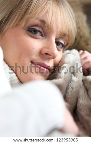 Woman sat relaxing with warm blanket - stock photo