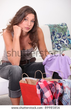 Woman sat with shopping bags - stock photo