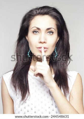Woman saying shh over grey background - stock photo