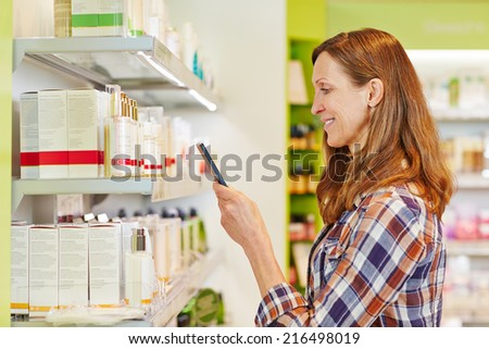 Woman scanning barcode of cosmetics in supermarket with her smartphone - stock photo