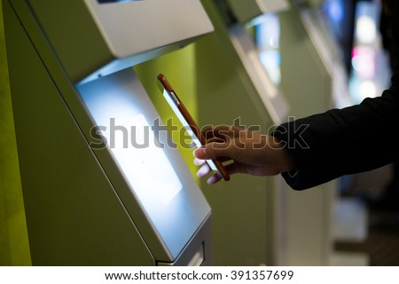 Woman scanning on the payment machine by NFC - stock photo