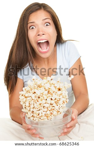 Woman scared funny watching scary movie. Beautiful girl watching movie in bed on white background - stock photo