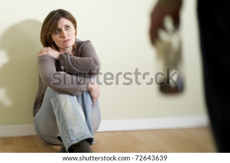 Woman scared of a man holding a bottle; Concept: abuse/domestic violence due to alcoholism - stock photo