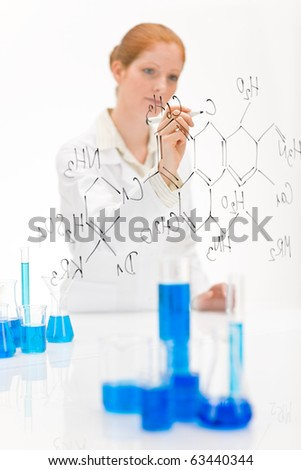 Woman scientist in laboratory write chemical formula with test tube and beaker - stock photo