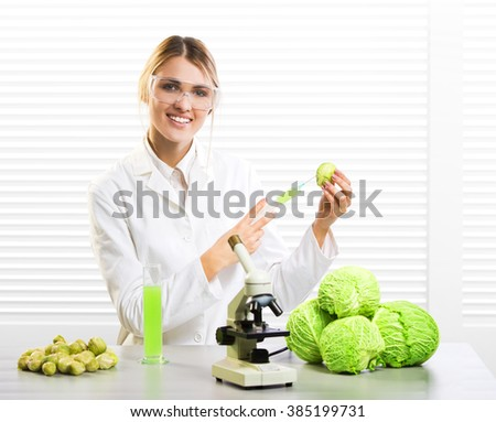 Woman scientist injecting cabbage with synthetic substances for growth; GM food - stock photo