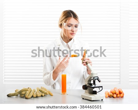 Woman scientist injecting vegetables with synthetic substances, color, vitamin etc; GM food - stock photo