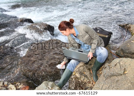Woman scientist testing quality of water in river - stock photo