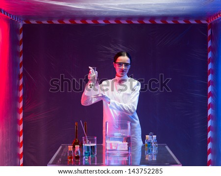 woman scientist wearing a white lab coat and protection goggles holding a bottle labeled bio hazardous with both hands in front of a table with glassware filled with chemicals, in a containment tent - stock photo