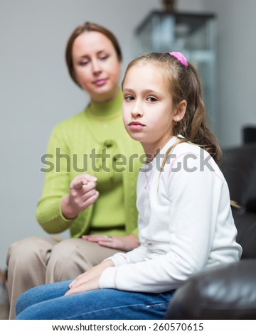 Woman scolding daughter at home interior  - stock photo