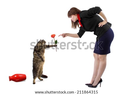 woman scolding pet cat that toppled a flower vase - stock photo