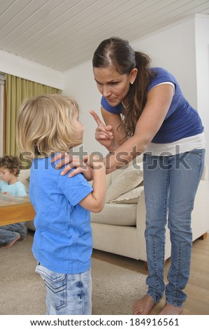 Woman scolds a young child in the home. Another child can be seen in the background