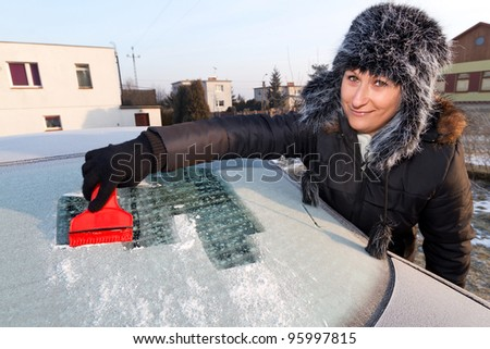 Woman scraping ice from the car window - stock photo
