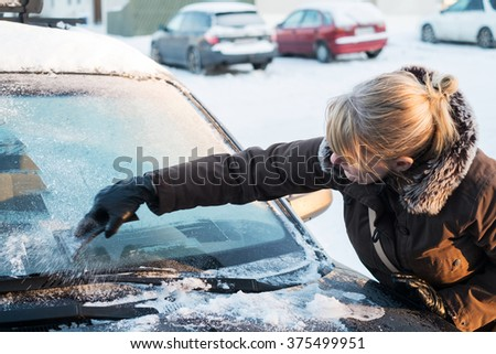 Woman scraping ice from the front window of her car on a cold winter morning