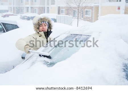 Woman scraping snow off of windshield - stock photo