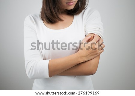 Woman scratching her arm. - stock photo