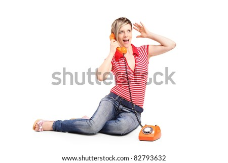 Woman screaming into the old style phone isolated on white background - stock photo