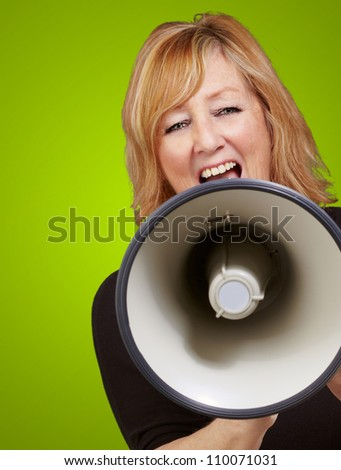 Woman screaming on a megaphone isolated on green background - stock photo
