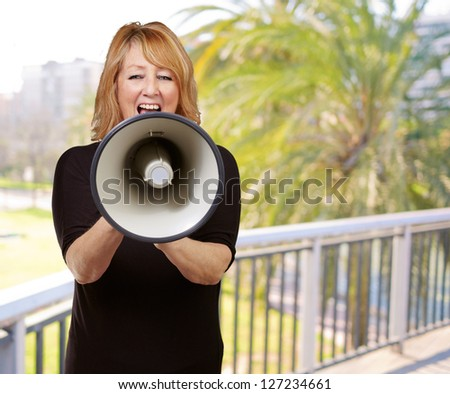 Woman screaming on a megaphone, outdoor - stock photo