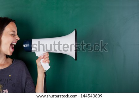 Woman screams into megaphone in front of a blackboard - stock photo