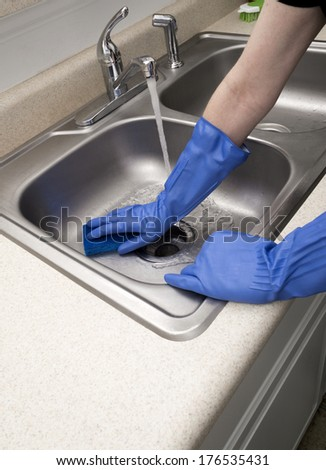 Woman Scrubbing Sink Wearing Blue Rubber Gloves/ Copy Space in Foreground/ Vertical Shot/ Water Running/ Stainless Steel Sink/ Chrome Faucet - stock photo