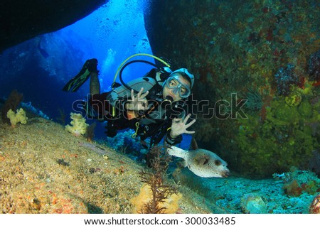 Woman scuba diver exploring underwater cavern and puffer fish - stock photo