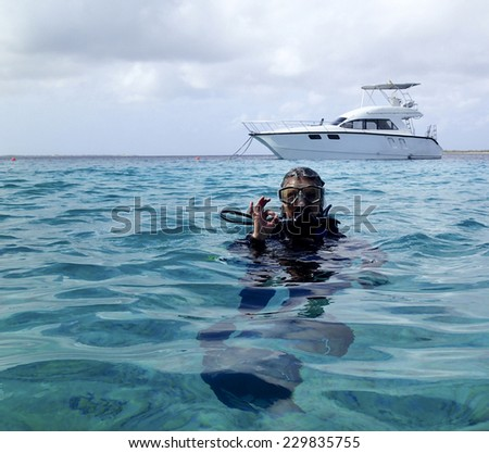 Woman scuba diver giving the O.K. sign on the surface after a tropical dive - stock photo