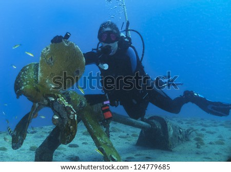 Woman scuba diver on the propeller of the Gregory, a wreck in St Maarten