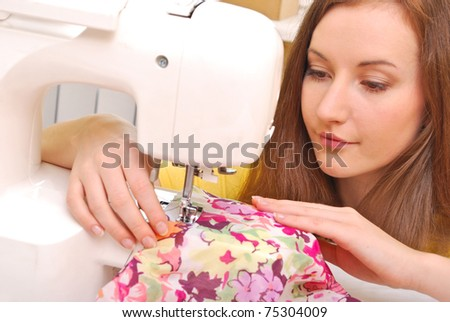 Woman seamstress work on the sewing-machine - stock photo