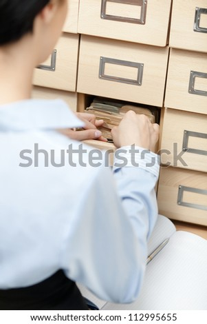 Woman searches something in card catalog composed of set of wood boxes at the library. Education and research