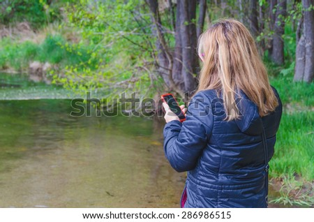 Woman searching network coverage near a river. Connectivity and telecommunications concept - stock photo