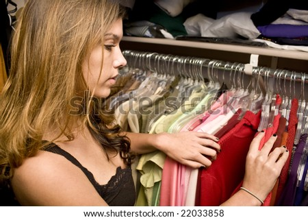 Woman searching through her closet looking for clothes - stock photo